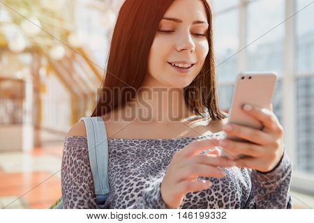Smiling Young Girl Using Modern Dual Camera Smart Phone