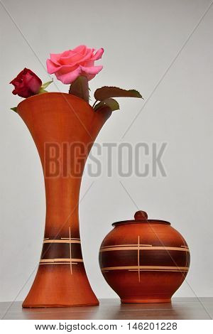 Two roses in a ceramic vase for flowers. The vase stands on a wooden base.