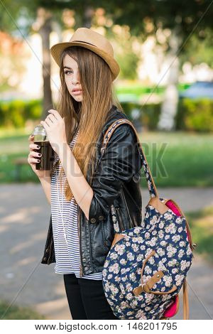 Cool millennial teenage girl drinking takeaway coffee in park in autumn. Beautiful young blonde Caucasian female student relaxing outdoors in fall. Natural light. Mild retouch.