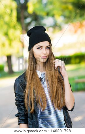 Beautiful teenage girl in park in autumn. Closeup outdoor portrait of gorgeous young blonde woman with headphones and beanie hat outdoors in fall. No retouch.