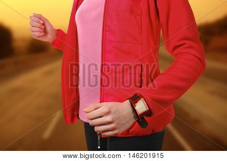Woman running with pulsometer on blurred road background