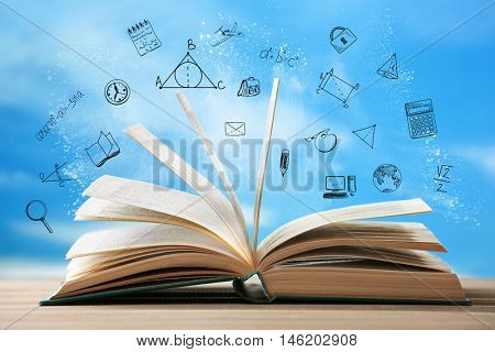 Book on wooden table. Icons on blurred sky background.