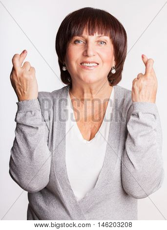 Mature woman with crossed fingers. Female showing a gesture with hands. Luck, wish