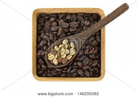Spoon of dried raw unroasted green coffee berry seeds on top of roasted coffee beans isolated on white background