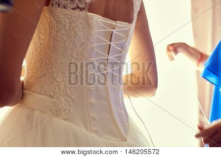 Closeup toned photo of beautiful bride tying up her wedding dress. Bridesmaid makes bow-knot on the back of brides wedding dress.