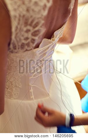 Bridesmaid makes bow-knot on the back of brides wedding dress. Closeup toned photo of beautiful bride tying up her wedding dress.