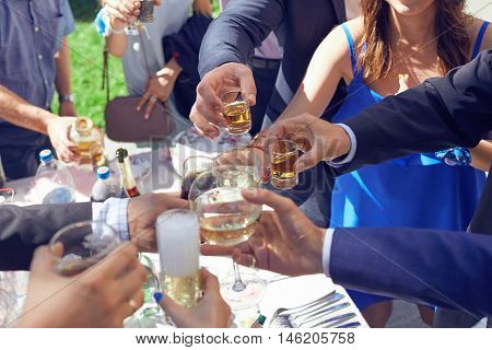 Young people having fun at a party with glasses of champagne. Holiday Event people cheering each other with champagne and wine.
