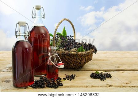 black elderberry juice in bottles and a basket with fresh fruits on rustic wooden boards against the blue sky with clouds copy space