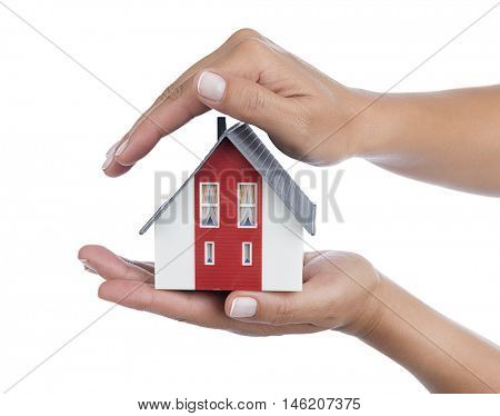 Model house in female hand isolated on white background - House production concept.