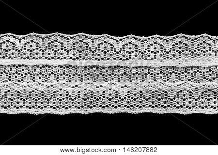 Strip of white vintage lace on black background