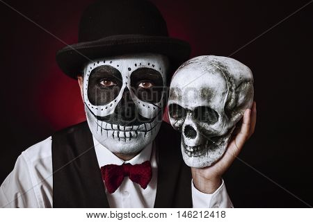 portrait of a young man with a mexican calaveras makeup, wearing bow tie and bowler hat, holding a skull in his hand next to his head