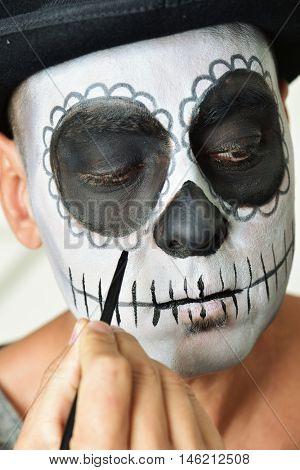 closeup of a young man making up himself as a mexican calaveras