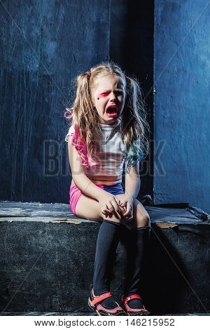 The crying crazy girl with grimace on black background