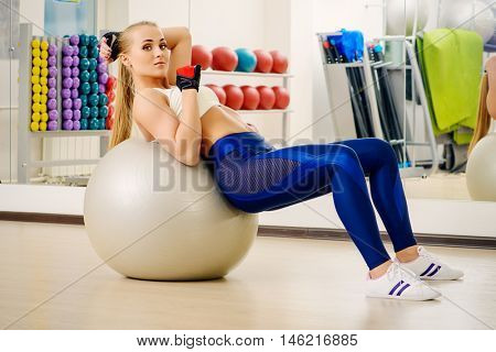 Sportive girl doing exercises with a fitness ball in the aerobics room. Active lifestyle. Body, healthcare. Fitness, gymnastics.