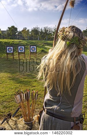 Medieval woman archer to use a bow and arrow and shoot at a target