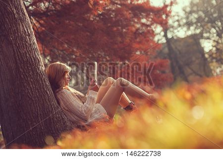 Beautiful young brunette sitting on a fallen autumn leaves in a park reading an e-book on a tablet computer