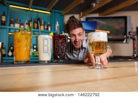 Young handsome Barman offers exotic sweet non-alcoholic cocktails in restaurant. Professional male bartender at work in bar made refreshing drinks. Selective focus on glass of cream soda