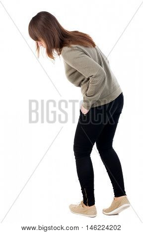 back view of standing young beautiful  woman in jeans looks down. girl  watching. Rear view people collection.  backside view of person.  Isolated over white background. The girl looks at his feet