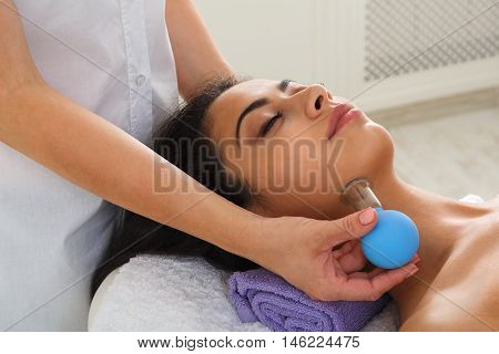 Vacuum massage in ayurveda spa. Female massagist with young woman patient in wellness center. Professional cosmetologist make health therapy to beautiful indian girl in beauty parlor.