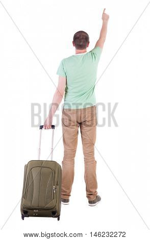 back view of  man  with suitcase. brunette guy pointing in motion.  backside view of person.  Rear view people collection. Isolated over white background. guy with a travel bag on wheels looking at