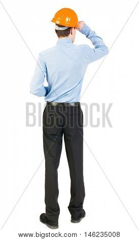 Backview of an engineer in construction helmet stands. Standing young guy. Rear view people collection.  backside view of person.  Isolated over white background. The man in trousers and shirt