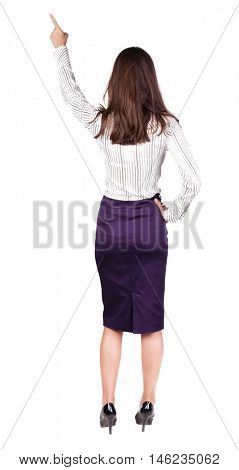 Back view of young brunette woman pointing at wall. beautiful girl in dress. Rear view people collection. backside view of person. Isolated over white background.