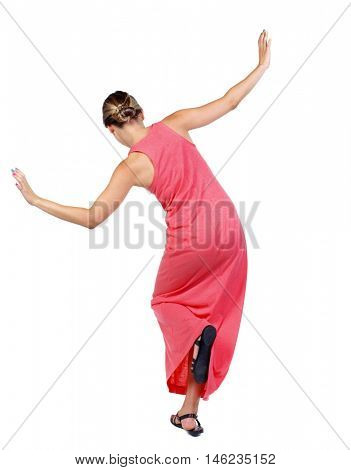 Balancing young woman. or dodge falling woman. slender woman in a long red dress is standing on one leg.