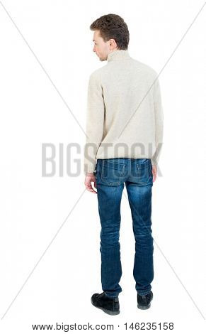 Back view of man . Curly short-haired man in a woolen white jacket looking sideways.
