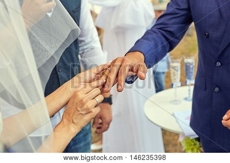 Bride putting a wedding ring on grooms finger. Beautiful place for outside wedding ceremony in wood.