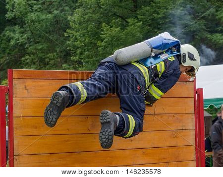 Firefighter overcomes wooden obstacle during the competition in fire sport.Contest TFA - Toughest Firefighter Alive