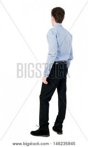 back view of Business man looks. curly-haired businessman in light shirt stands sideways and looks forward.