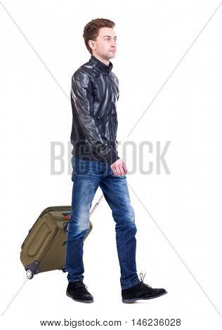 front view of walking man with suitcase. brunette guy in motion. Curly guy in a black leather jacket goes to the side with a suitcase on wheels.