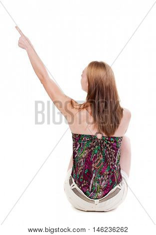 Back view of  sitting pointing woman. beautiful blonde girl. Rear view people collection.  backside view of person.  Isolated over white background.