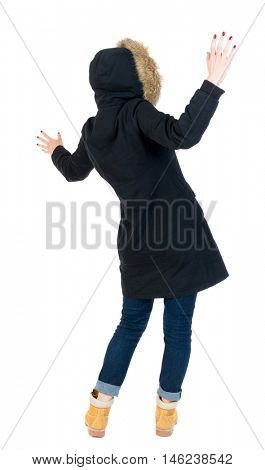 Back view woman in winter jacket Balances waving his arms. The girl in warm winter jacket, black, surprised her arms.