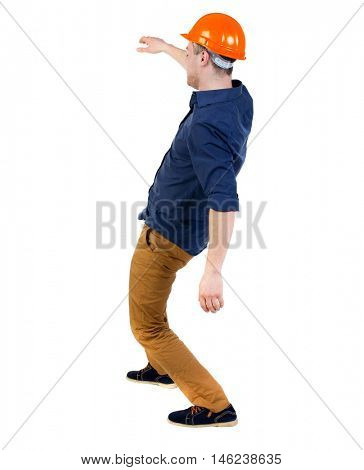 Balancing young man. or dodge the falling man. backside view of person. Isolated over white background. a man in a protective helmet falls