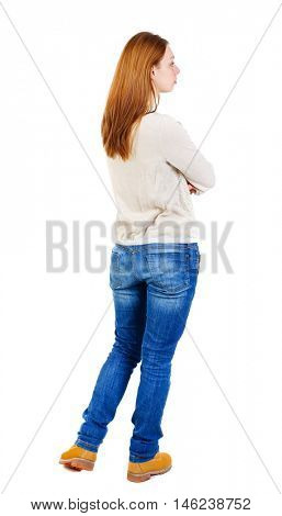 back view of standing young beautiful woman. Girl in a white jacket standing with arms folded and looking to the left.