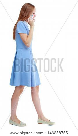 side view of a woman walking with a mobile phone. Rear view people collection. Isolated over white background. Skinny girl in blue dress talking while walking.