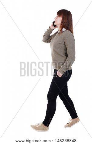 side view of a woman walking with a mobile phone. back view of girl in motion. She goes right on the phone