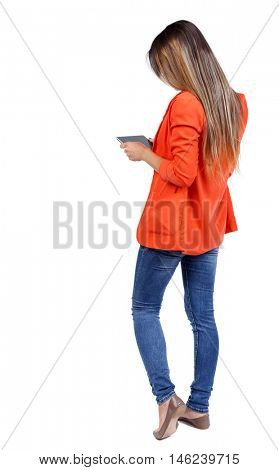 back view of standing young beautiful woman using a mobile phone or tablet computer. girl in a red jacket standing sideways and looking at the tablet.