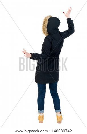 Back view woman in winter jacket Balances waving his arms. Standing young girl in parka. Girl in warm winter black jacket waving his arms.