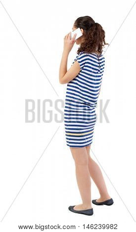 back view of a woman talking on the phone. Swarthy girl in a checkered dress talking on the white smartphone.