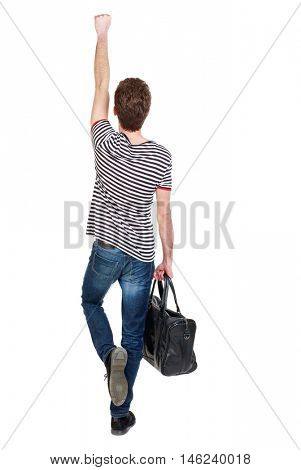 Back view of man with bag. Curly boy in a striped vest holding a bag in his hand and raising his arm above his head.