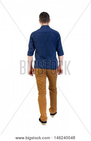 Back view of going handsome man. walking young guy . man in a blue shirt with the sleeves rolled up out of the frame.