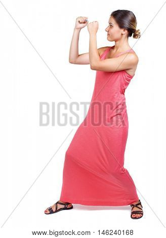 skinny woman funny fights waving his arms and legs. slender woman in a long red dress in boxing pose.