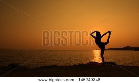 Girl is standing yoga posture beautiful sunset