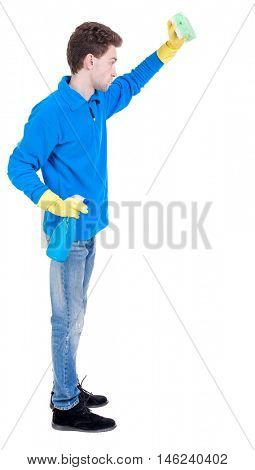 side view of a cleaner man in gloves with sponge and detergent. girl watching. Curly boy in a warm blue sweater in the cleaning process.