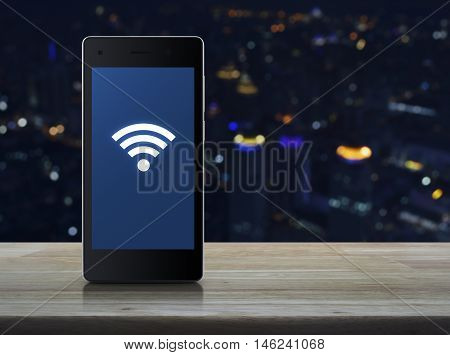 Wi-fi connection icon on modern smart phone screen on wooden table over blur light city tower Technology and internet concept