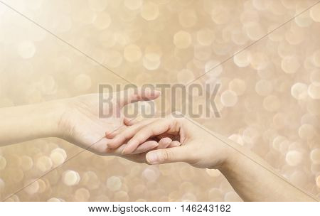 Closeup woman hand hold another woman hand for console and encourage in tender emotion on abstract blurred brown light spot bokeh textured background