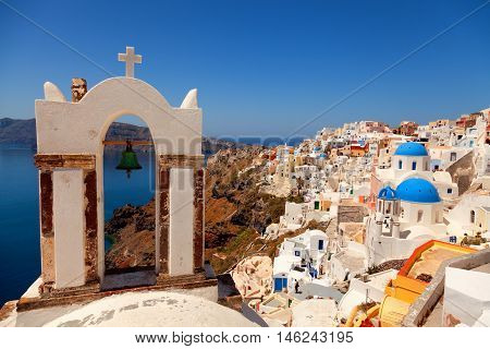 Landscape of Oia town in Santorini Greece with blue dome churches and cross on foreground.