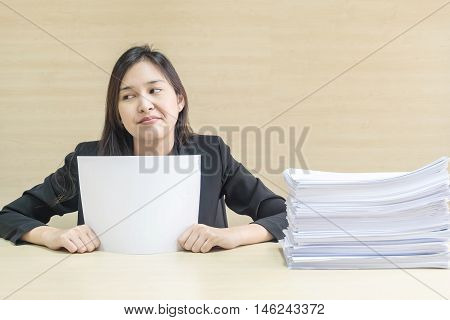 Closeup working woman are boring from pile of work paper in front of her in work concept on blurred wooden desk and wooden wall textured background in the meeting room under window light